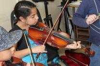 Niños realizan su mejor esfuerzo en las clases de música.