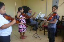 Niños practicando ejecución del violín.