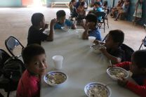 Niños del comedor infantil recibiendo alimentos
