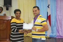 La Directora Evet Clachar entregando medalla al primer puesto Agusto Grajales