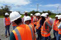 Estudiantes en campo abierto recibiendo charla sobre el funcionamiento del parque eólico.