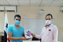 Estudiante recibe tablets que le entrega el Director del Centro.