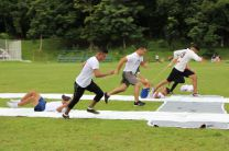 Jóvenes corren y deslizan a su compañero en concurso.