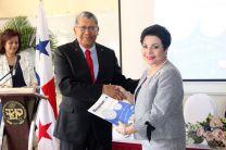 """El Dr. Dimas E. Portillo, autor del libro """"Mecanismo, Guía de Laboratorio, entrega un ejemplar a la Rectora Encargada de la UTP."""