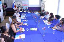 Asistentes a la Rueda de prensa alrededor de una mesa con mantel azul.