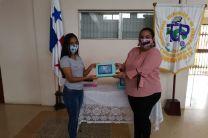 La Jefa de Servicios Generales, entrega tablets a estudiante.