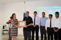 Coordinadora del Proyecto Ing. María Tejedor entrega reconocimiento a Monseñor Edgardo Cedeño.