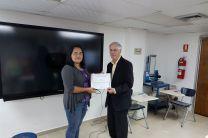 La Ingeniera Jessie Abrego, docente de la FIM, entrega certificado al expositor Dr. John Sullivan