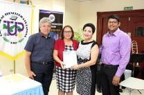 María Herrera, hermana del Prof. José Herrera (q.e.p.d), recibió un libro de manos de la Rectora Alma Urriola de Muñoz.