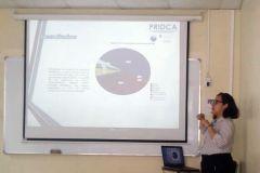 Karina García, en el aula de sustentación presentando un PowerPoint, en una pantalla..