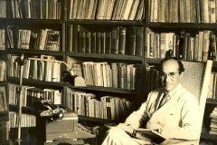 Rogelio Sinan junto a su biblioteca personal, que ahora está en las instalaciones de la UTP.