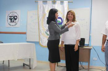 Directora del Centro entrega pines a colaboradores.