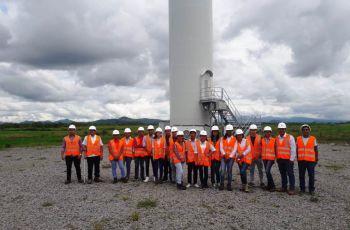 Grupo de estudiantes junto a uno de los aerogeneradores, acompañados por el profesor Félix  Tejeira.