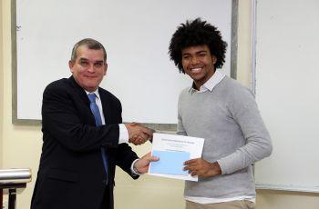 El Dr. Julio Rodríguez, Decano de la FIM, entrega reconocimiento al estudiante José Alejandro Rodríguez.