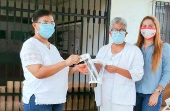 La Licda. Raquel Guevara e Ing. Yaneth Gutiérrez entregan a la Dra. Itza Camargo, máscaras faciales.