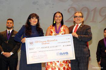 El Rector y Yamileth Velásquez, de ASSA, entregan premio a ganadora del Concurso de Oratoria.